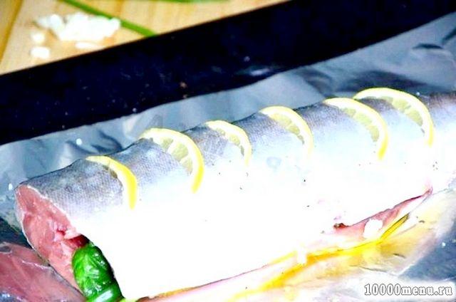 Фото - У надрізи вкладаємо скибочки лимона. Зверху поливаємо залишилися оливковою олією. Загортаємо рибу у фольгу. Запікаємо в розігрітій до 190 С духовці до готовності близько 30 хвилин.